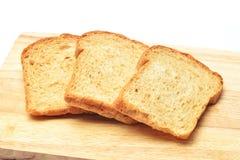 三片面包片在木切板的在白色背景中 库存图片