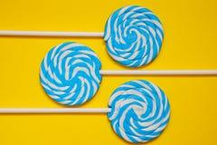 三白色和在黄色背景的蓝色棒棒糖 图库摄影