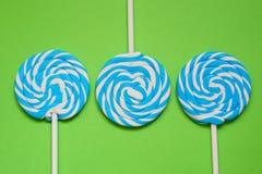 三白色和在绿色背景的蓝色棒棒糖 免版税库存图片