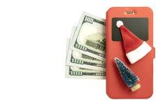 三百美元,一个智能手机在红色盒、圣诞树和圣诞老人项目纪念品和在白色背景 的treadled 免版税图库摄影
