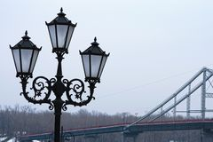 三盏灯的美丽的黑街道灯笼,照片的关闭 步行桥在背景中 冬天早晨视图 免版税库存图片