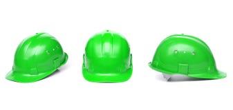 三相同绿色安全帽。 免版税库存图片