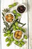 三种类在瓷碗和年轻橄榄色的枝杈的橄榄 库存图片