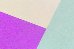 三种颜色的背景绿化,紫色和黄色发光的纸 免版税库存照片