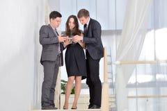 三站立在台阶的商人解决业务问题 库存照片