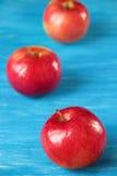 三红色在一张蓝色桌上的苹果计算机 免版税库存图片