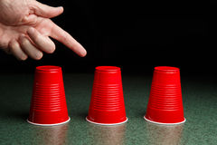三红色杯和一只指向的手 免版税库存照片
