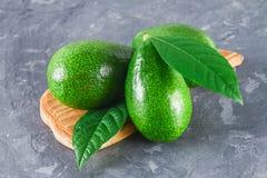 三绿色未加工的成熟鲕梨果子和裁减半与有叶子的一根骨头在一张灰色黑暗的具体桌上的一个木切板 库存图片