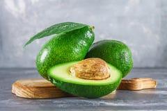 三绿色未加工的成熟鲕梨果子和裁减半与有叶子的一根骨头在一张灰色黑暗的具体桌上的一个木切板 免版税库存照片