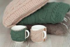 三编织了枕头和两个杯子在木板背景 免版税图库摄影