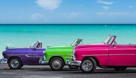 三美国经典敞蓬车汽车在巴拉德罗角- Serie Kuba 2016年报告文学的海滩停放了 免版税图库摄影