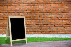 三脚架黑板在有铸工砖墙的内部屋子里 库存照片