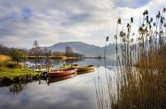 三艘划艇休息在一个镇静湖一边 免版税库存图片