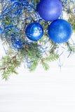 三蓝色和紫罗兰色Xmas球和枝杈在纸 免版税库存照片