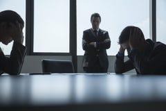 三被挫败的和劳累过度的商人在有胳膊的证券交易经纪人行情室横渡和顶头在手上。 库存照片