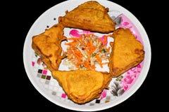 三角在一块板材的形状面包Pakora在黑背景用切的沙拉 免版税图库摄影