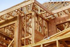 三角形屋顶特写镜头在棍子的修造了有木捆、岗位和射线框架的家庭建设中新的修造屋顶 免版税库存照片
