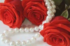 三说谎在白色背景的英国兰开斯特家族族徽特写镜头白色珍珠neklace 宏指令 免版税库存图片