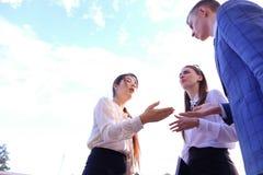 三谈话美丽的聪明的年轻的商人,握手, 库存照片