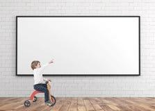 三轮车的逗人喜爱的男孩,显示手指whiteboard 库存照片