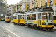 三辆典型的黄色电车在商务正方形停放了在里斯本 库存照片
