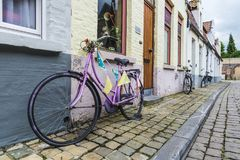 三辆老自行车在一条街道上停放了在布鲁日,比利时 免版税库存照片