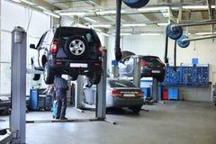 三辆黑汽车在小服务站和两个人站立 免版税库存照片