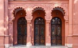 三连续成拱形木门在乌日戈罗德,乌克兰犹太教堂红色门面  免版税图库摄影