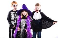 三逗人喜爱的孩子穿戴了万圣夜服装:巫婆,骨骼,吸血鬼 免版税图库摄影
