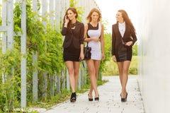 三重要和步行沿着向下街道的成功的女商人 库存图片