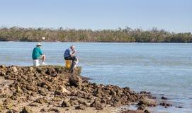 三钓鱼,两个人和一伟大蓝色的苍鹭的巢Ardea herodias每 免版税库存照片