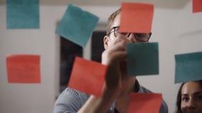 三青年人队-玻璃的年轻人黏附色的papper并且做笔记对此 工友,当时 股票录像