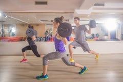 三青年人健身房刺衡量酒吧妇女人 免版税图库摄影