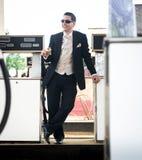 三件套的英俊的人在加油站喝威士忌酒的 免版税图库摄影