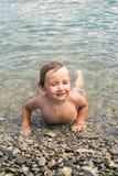 三年的男孩在小卵石的海沐浴 库存照片