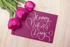 三紫色郁金香与卡片和文本愉快的母亲节 书法字法手凹道 免版税库存照片
