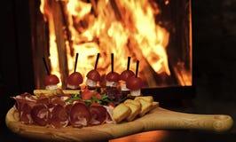 上与在木桌,在背景的火上的快餐 冷的开胃菜用蕃茄,香肠,蒜味咸腊肠,火腿,芝麻菜 库存照片