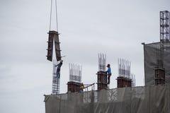 登上与起重机的建筑工人具体模板在期间 免版税图库摄影