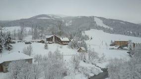 上升上面喀尔巴阡山脉的一个村庄 鸟` s积雪的房子眼睛视图山的 农村的横向 股票录像