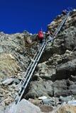 上升下来一架陡峭的梯子的登山家 免版税图库摄影