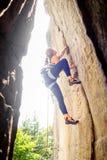 上升与在岩石墙壁上的绳索的女性登山人 库存照片