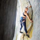 上升与在岩石墙壁上的绳索的女性登山人 免版税库存图片