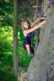 上升与在岩石墙壁上的绳索的女性登山人 免版税库存照片