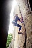 上升与在岩石墙壁上的绳索的女性登山人 免版税图库摄影
