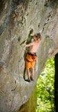 上升与在岩石墙壁上的绳索的男性攀岩运动员 库存图片