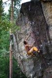 上升与绳索和马枪的年轻男性登山人,寻找在大岩石墙壁上的下个夹子 新的成人 轴上升的设备冰的山 库存图片