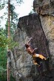 上升与绳索和马枪的年轻男性登山人,寻找在大岩石墙壁上的下个夹子 新的成人 轴上升的设备冰的山 免版税库存照片