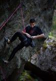 上升与绳索和马枪的年轻男性登山人,寻找在大岩石墙壁上的下个夹子 新的成人 轴上升的设备冰的山 免版税库存图片