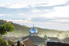 上升入与云彩的天空的清真寺和大山的圆顶 库存照片