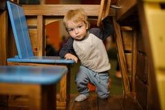 上升入玩具木汽车的逗人喜爱的小男孩 免版税库存图片